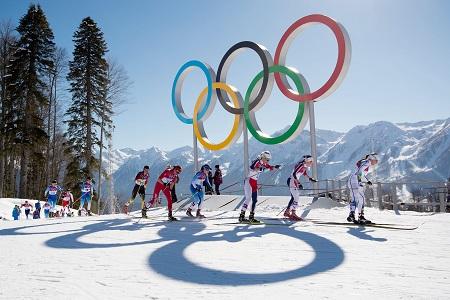De kopgroep passeert de olympische ringen tijdens de skiathlon voor dames (PRO SHOTS/Witters)