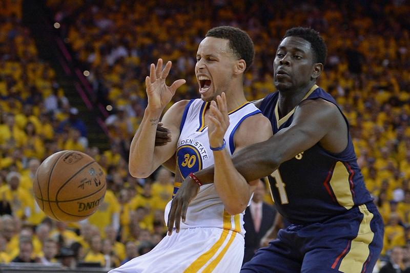 Golden State Warriors-speler Stephen Curry is een stevig duel met New Orleans Pelicans-speler Jrue Holiday verwikkeld. Wat zou een goed onderschrift zijn bij deze foto? (PRO SHOTS/Zuma Sports Wire)