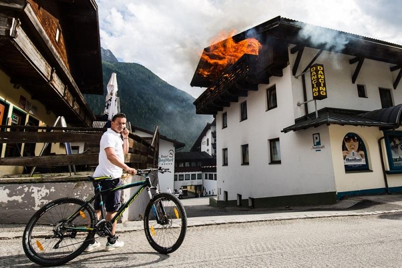 Terwijl het hotel naast het hotel waar Ajax verblijft in brand staat, pleegt Marc Overmars in alle rust een telefoontje. Wat zou een goed onderschrift zijn bij deze foto? (Pro Shots/Erwin Spek)