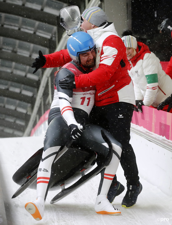 Wolfgang Kindl trekt teamgenoot David Gleirscher van zijn slee nadat een olympische medaille zeker was, waarna het zelfs nog goud bleek te worden (Pro Shots/Action Images)