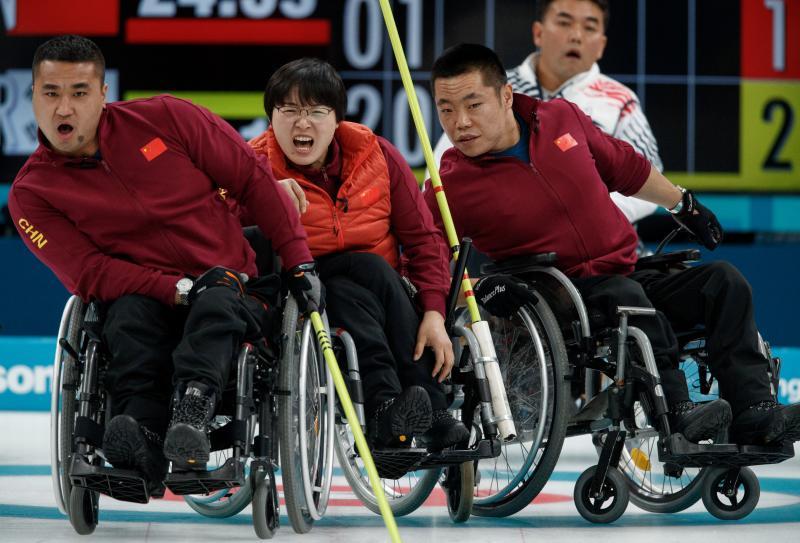 Vol spanning kijken Wang Haitao, Wang Meng en Liu Wei van de Chinese paralympische curlingploeg naar wat er gebeurd. Wat zou een leuk onderschrift zijn bij deze foto? (Pro Shots / Action Images)