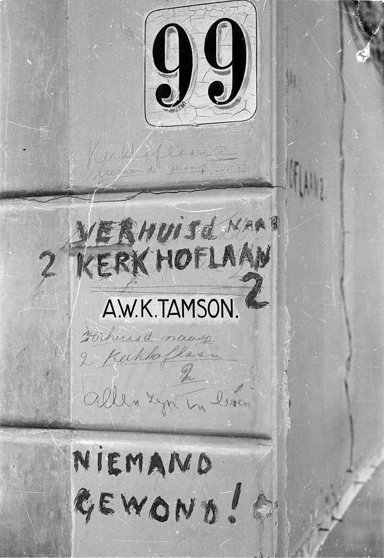 Opschrift naast de voordeur van het woonhuis aan de Riouwstraat 99 te Den Haag na een V2-inslag op 25 januari 1945. De bewoners, Familie A. Tamson, zijn niet gewond geraakt, maar het huis is wel flink beschadigd.