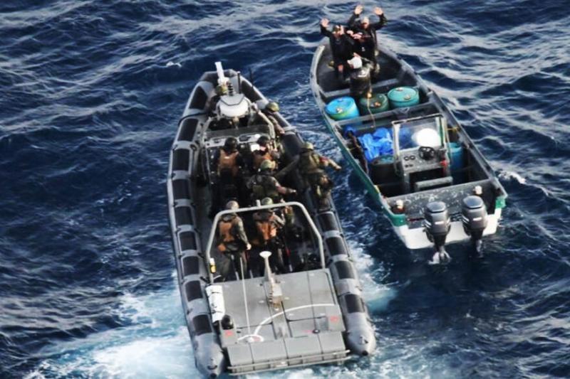 De opvarenden van de smokkelboot worden aangehouden (Foto: Defensie)