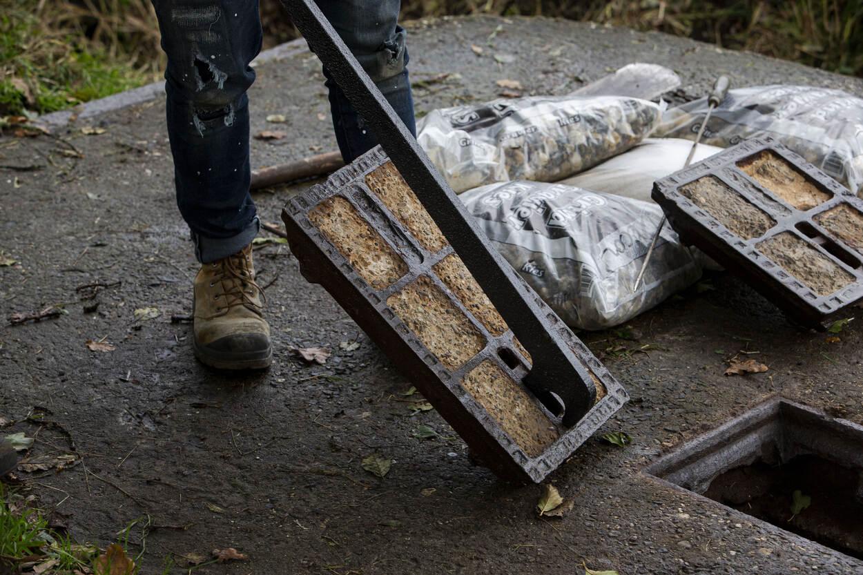 Met een op maat gemaakte tang worden originele deksels op de gaten geplaatst. De deksels zijn gevonden bij een gesloopte versperring in Nijmegen.