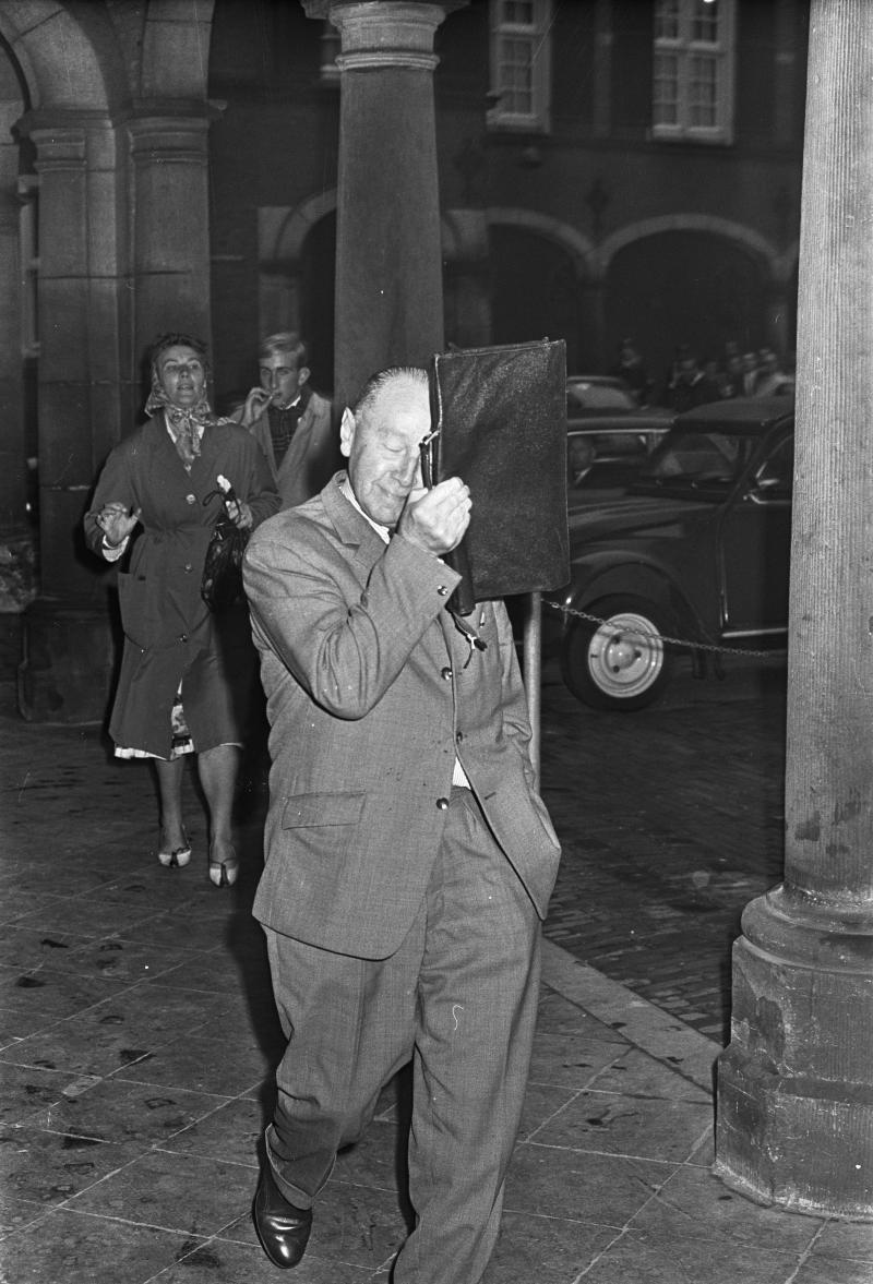 Dhr. Hendrik Adams verlaat de Eerste Kamer met zijn tas voor zijn gezicht na het handgemeen met Jan Baas (WikiCommons/Fotograaf Onbekend/Anefo)